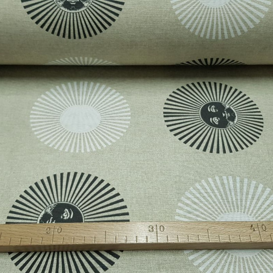 Canvas Suns White Black fabric - Decorative canvas fabric, ideal for cushions, curtains and other home decoration. Drawings of suns with black and white faces appear on the fabric on a beige background. The fabric is 280cm wide and its composition 7