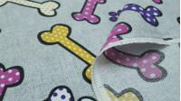 Tela Loneta Huesos Huellas Topos - Tela de loneta fuerte y resistente con dibujos de huesos y huellas de perros en varios colores con topos, sobre un fondo de color gris. La tela mide 280cm de ancho y su composición 50% algodón –50% poliester.