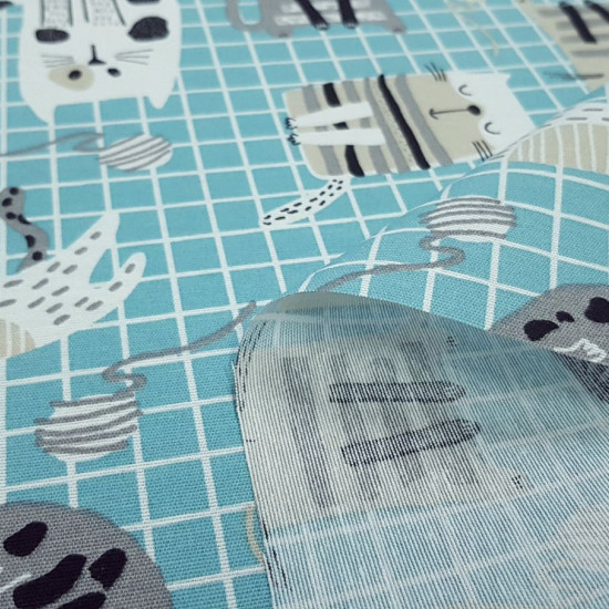 Canvas Cats Grids Blue fabric - Decorative canvas fabric with cat drawings on a turquoise blue grid background. The fabric is 280cm wide and its composition is 70% cotton - 30% polyester.