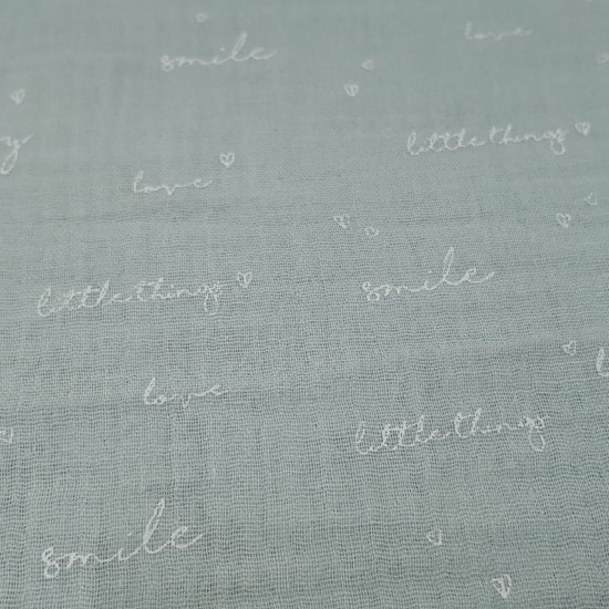 """Tela Doble Gasa Frases Jade - Tela fina de doble gasa o muselina con dibujos de frases como """"littlethings"""", """"love"""", """"smile"""" y """"happy"""" alternando con corazones pequeñitos sobre un fondo verde jade. La tela mide 130cm de ancho y su composición 100%"""