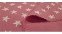 Tela Doble Gasa Estrellas Blancas Rosa - Tela de doble gasa o muselina de algodón infantil con dibujos de estrellas blancas sobre un fondo de color rosa. La tela mide 130cm de ancho y su composición 100% algodón.