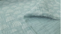 Double Gauze Rainbow Mint fabric - Double gauze or muslin fabric with white outlined rainbow patterns on a mint green background. The fabric is 130cm wide and its composition is 100% cotton.