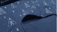 Double Gauze Tipis Feathers fabric - Double gauze or muslin fabric with drawings of tents or tipis and feathers on a dark blue background. The fabric is 135cm wide and its composition is 100% cotton.