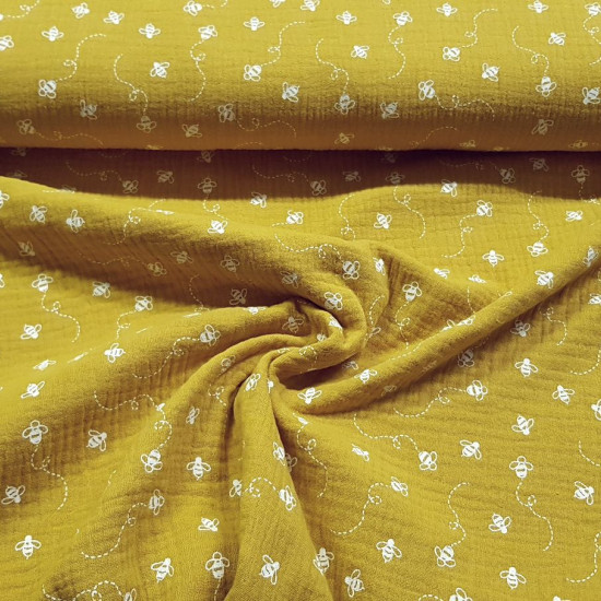 Double Gauze Bees fabric - Very light double gauze or muslin fabric with drawings of bees on an ocher background. The fabric is 135cm wide and its composition is 100% cotton.