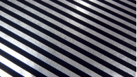OUTLET Foil Silver Stripes fabric - Fine and very bright laminated fabric. Highlights the fall of the fabric and its brightness, which make it very striking in any costume. This fabric draws silver stripes on a black background. The fabric is 110cm wid