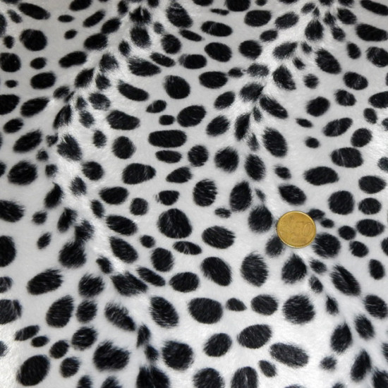 Tela Pelo Mutón Dálmata - Tejido de pelo corto tipo mutón con dibujo estampado de pintas negras imitando a la de un perro dálmata. La tela mide 150cm de ancho y su composición 100% poliester.